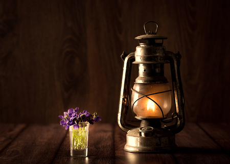 Spring concept with violet and oil lamp on wooden background