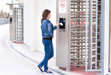 Young woman puts the card into the reader access