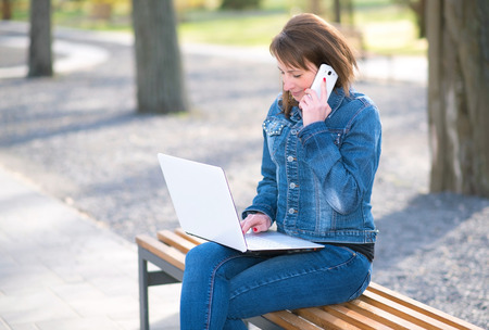 Cute woman sitting on the bench and working her notebook Stock Photo