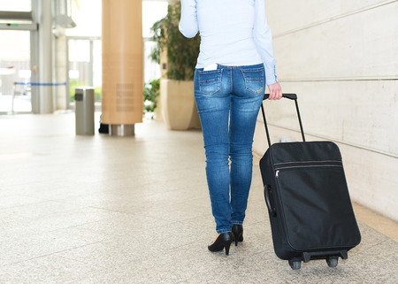 collegian: Traveler woman walking her suitcase at the airport Stock Photo