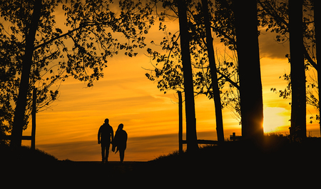 Lover couple silhouette the sunset. Dark toned photo Stock Photo