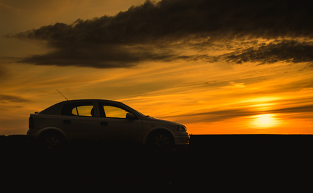 sedan: Car silhouette in sunset. Nature photo with car