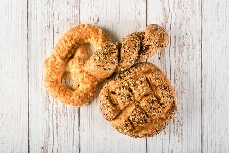 Fresh seedy breads on a white wooden background