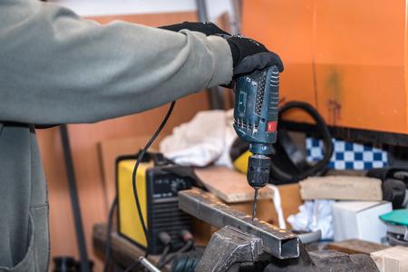 Werknemer oefent een gat in een metalen voorwerp