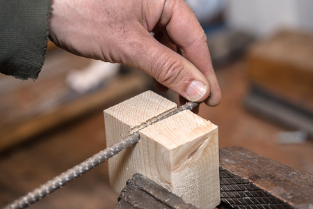 Rasp in the rugged hands of a skilled carpenter. Closeup photo Stock Photo