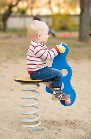 Adorable blond hair child in the playground