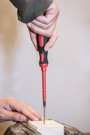 Worker is screwing a screw into wooden workpiece with the screwdriver