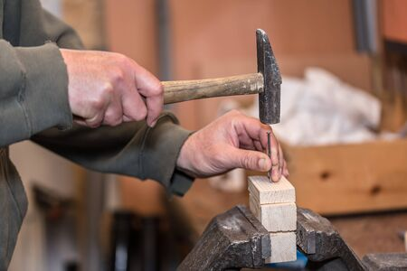 Wooden workpiece on the vise. Man working with wooden.