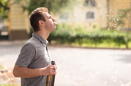 Young man spit out alcohol in the park