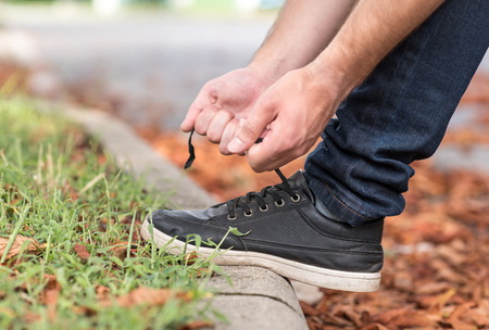 Mens shoes tying shoelaces in park Фото со стока