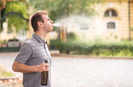 Un jeune homme crache de l'alcool dans le parc Banque d'images - 84650434