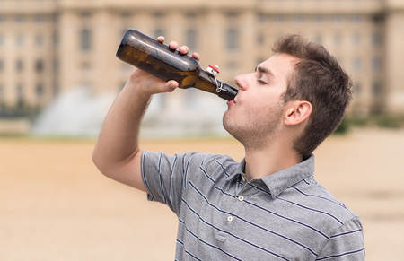 Young man drink a bottle of beer in the public park