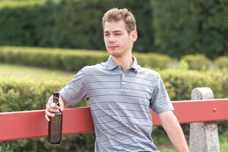 Young man sitting on bench with a bottle of beer in the park Stock Photo