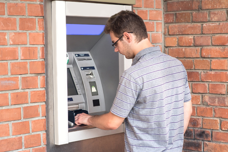 Photo of man using ATM bank machine