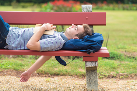 Young man sleeping in the park on the bench with a book Stock Photo