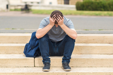 Sad man sitting on stairs in the park Stock Photo