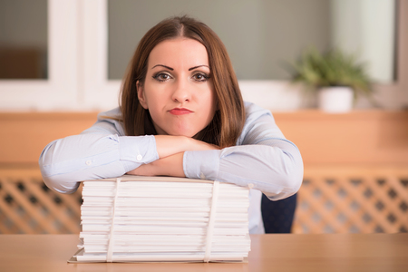 Phlegmatic resting on heap of documents in the office Stock Photo