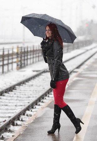 Beautiful young woman waiting for a train in the station