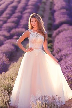 Beautiful bride in wedding day in lavender field. Beautiful blond woman