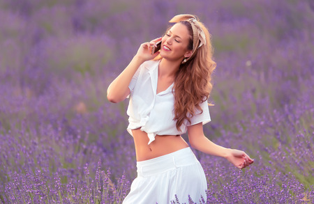 Beautiful woman use her phone in the lavender field a summers day Stockfoto