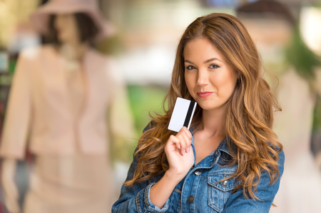 Beauty woman with credit card before the shop