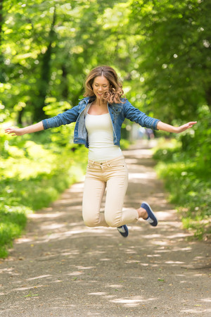 Young happy woman jumping in the green park Stock Photo