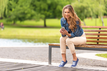 Young woman sitting on bench and use her phone in the park Stock Photo