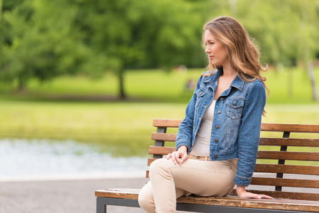 Young woman sitting on bench in the park Stock Photo