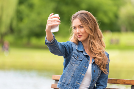 Beauty woman taking selfie with her phone in the nature