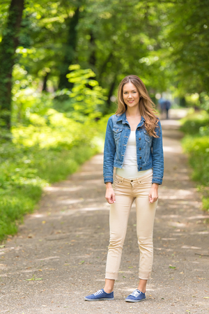 Young woman in the green forest. Standing on walkway
