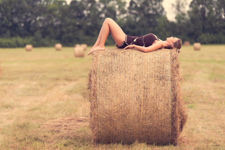 Beautiful woman relaxing on hay bale in summer