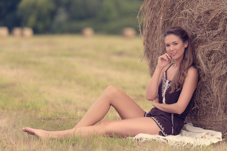 Portrait of a beautiful woman with hay bale in summer