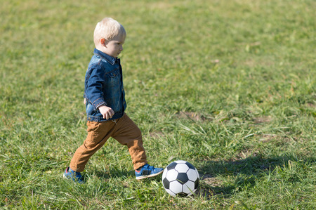 Adorable little child play football in the park