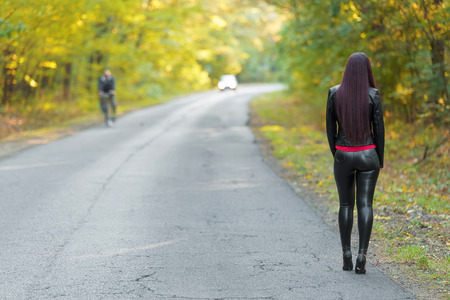 Pretty woman walking on the road near the forest