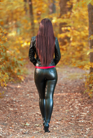 Pretty woman in the autumn forest. Back view 免版税图像