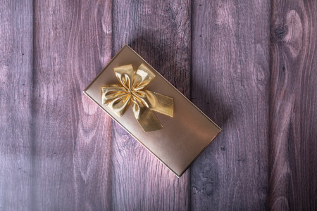 Golden gift box on wooden textured background 스톡 콘텐츠 - 122802041