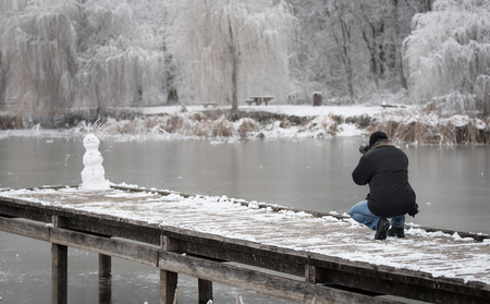Nature photographer take a photo of a snowman a winters day