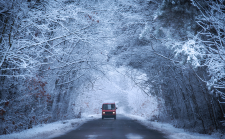 Red car on the winter road in the forest. Blue toned photo 스톡 콘텐츠 - 124277028