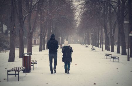 Couple walking in the winter park. Dark toned photo