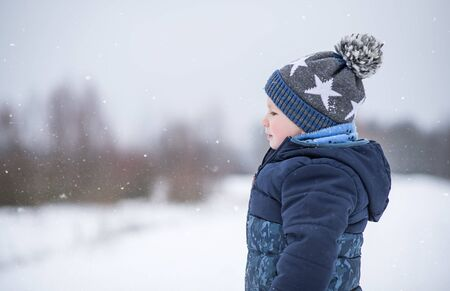 Little boy in the snowy nature a winters day