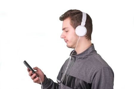 Handsome man searching music on his phone a white background