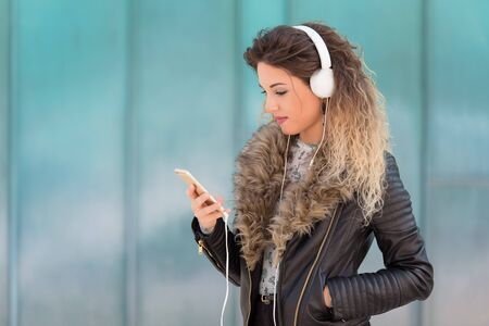 Young woman listening music with her headphones in the street