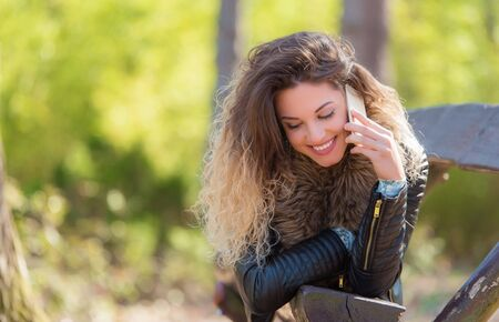 Beautiful woman relaxing and use smartphone in the park