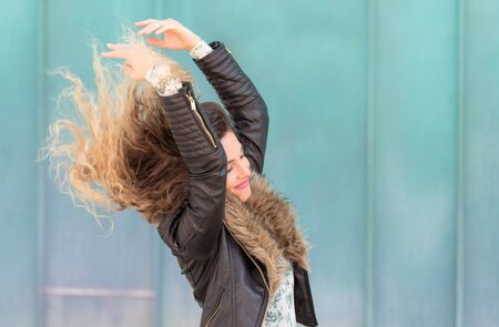 Happy young woman play her hair on light blue background Stock Photo
