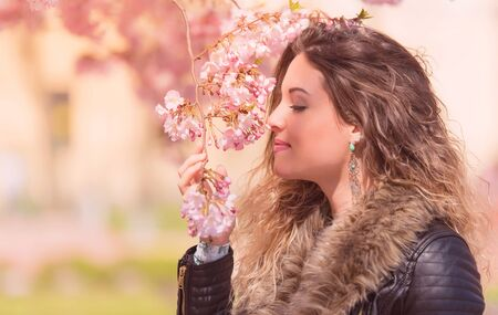 Beautiful woman smelling flowers in the garden