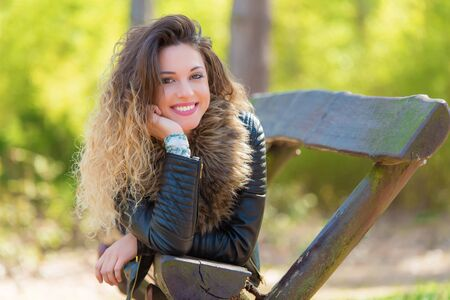 Beautiful woman relaxing on bench in the park