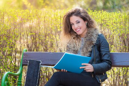 Beautiful student sitting on a bench in the park and learning Stock Photo