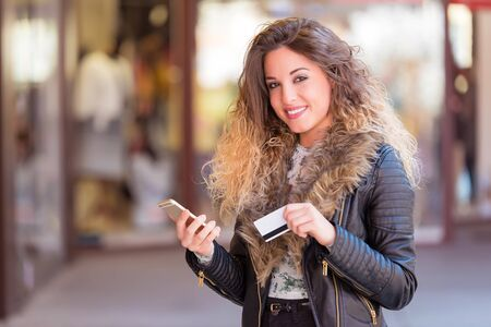 Beautiful woman using cell phone and holding credit card before the shop