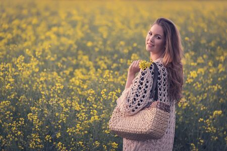 Beautiful woman in rapeseed field. Soft toned photo