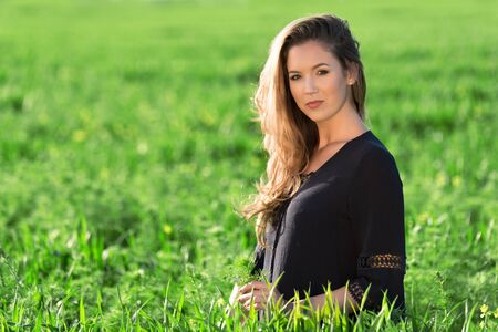 Beautiful woman on a green wheat field